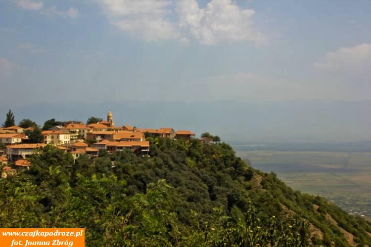 """1. Miasto Signagi. Niewiadomo dlaczego nazywane """" miastem miłości"""". Pięknie odnowione, awłaściwie zbudowane odnowa, posadowione nasporym wzniesieniu, góruje nadRówniną Alazańską skąd wpogodny dzień dostrzec można piętrzące się szczyty Wielkiego Kaukazu."""