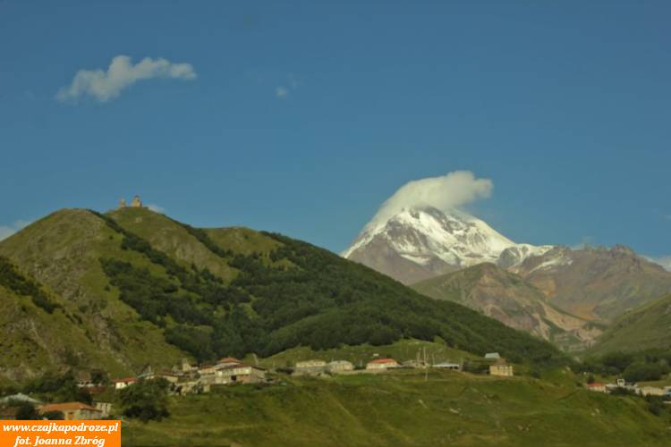 Zmiasteczka Kazbegi widać już pokryty śniegiem ichmurami szczyt Kazbek owysokości 5047m n.p.m. Nadwidoczną wioską Gergeti usadowiła się światynia Cminda Sameba. Gruzini często budują swoje świątynie nawysokich górach bybyć bliżej Boga.