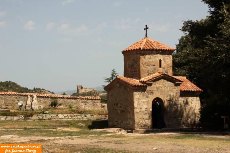 Miniaturowa cerkiew wSamtawro awoddali widać ruiny średniowiecznej twierdzy Berbiscyche.